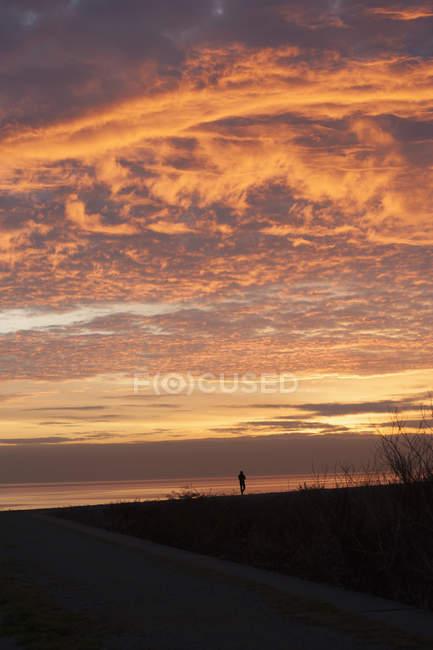 Silhouette de paysage dans le ciel nuageux au coucher du soleil — Photo de stock