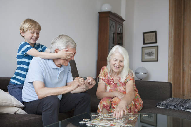 Boy covering grandfathers eyes while senior woman arranging jigsaw puzzle at table in living room — Stock Photo