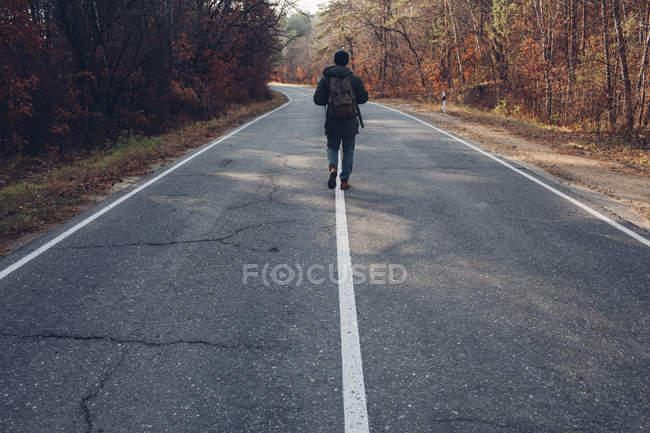 Вид сзади на пешехода, идущего по проселочной дороге — стоковое фото