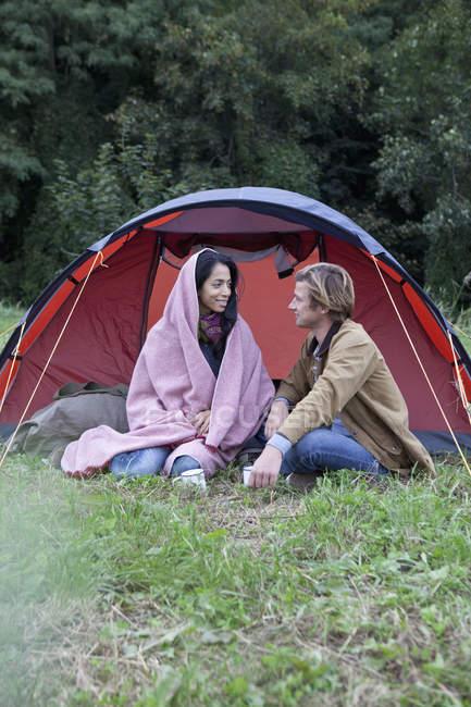 Jovem casal sentado perto de barraca cúpula na natureza — Fotografia de Stock