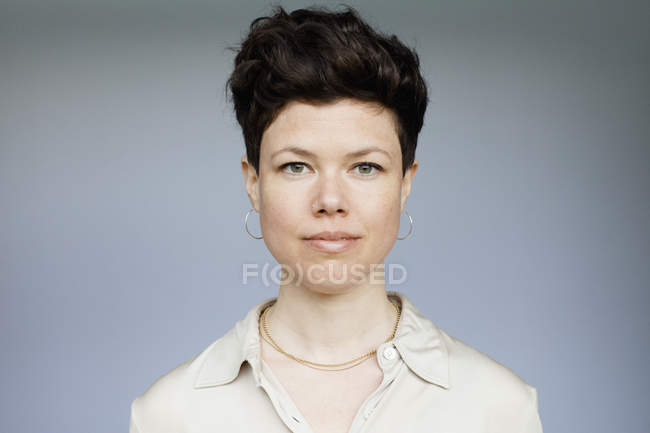 Portrait of confident mid adult woman against gray background — Stock Photo