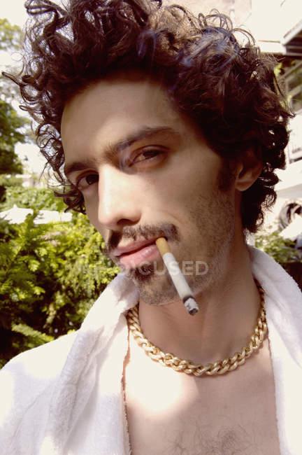 Mann im Frottee-Mantel rauchend — Stockfoto