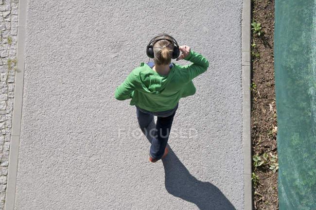 Dessus vue de femme portant casque et marcher sur le trottoir — Photo de stock