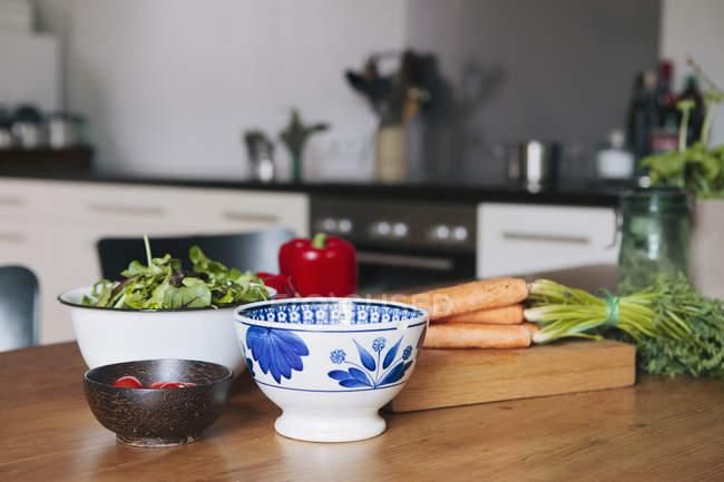 Крупным планом вид овощей и миски на деревянном столе в кухне — стоковое фото