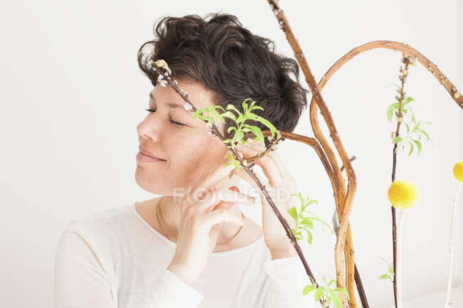 Close-up de mulher tocando planta contra fundo branco — Fotografia de Stock