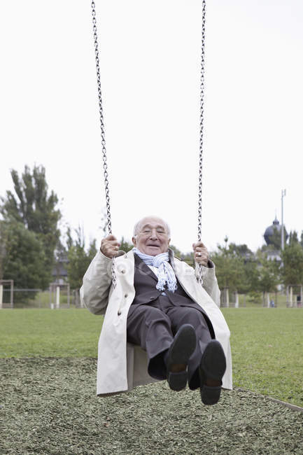 Playful senior man swinging in park — Stock Photo