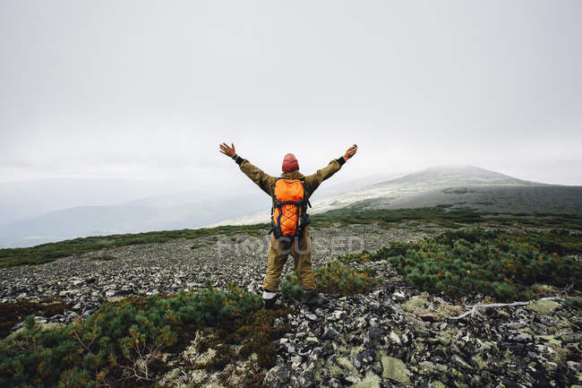 Rear view of man standing with arms outstretched on mountain — Stock Photo