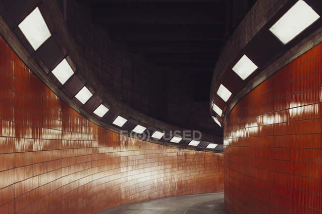 Passerelle éclairée dans un tunnel avec murs carrelés — Photo de stock