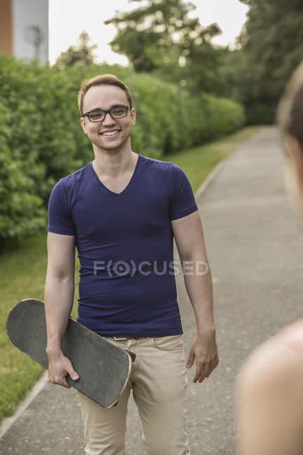 Jovem feliz segurando skate enquanto olha para a mulher no parque — Fotografia de Stock