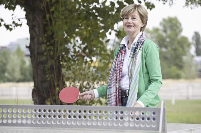 Sorridente donna matura che gioca a ping pong — Foto stock