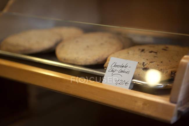 Etiqueta de preço na bandeja de biscoitos de chocolate no armário de exposição de café — Fotografia de Stock