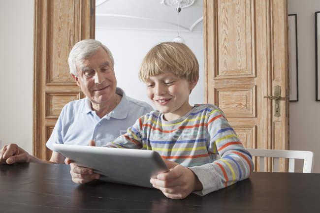 Senior homme regardant petit-fils en utilisant une tablette numérique dans la maison — Photo de stock