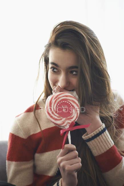 Mädchen halten Lutscher und den Mund mit der Hand zu Hause — Stockfoto