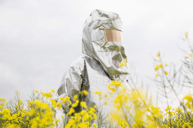 Person in radiation protective suit standing in poilseed rape field — Stock Photo