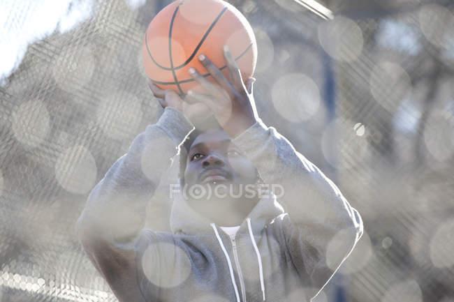 Hombre joven con el objetivo de baloncesto mientras que está parado en la cancha de básquet - foto de stock