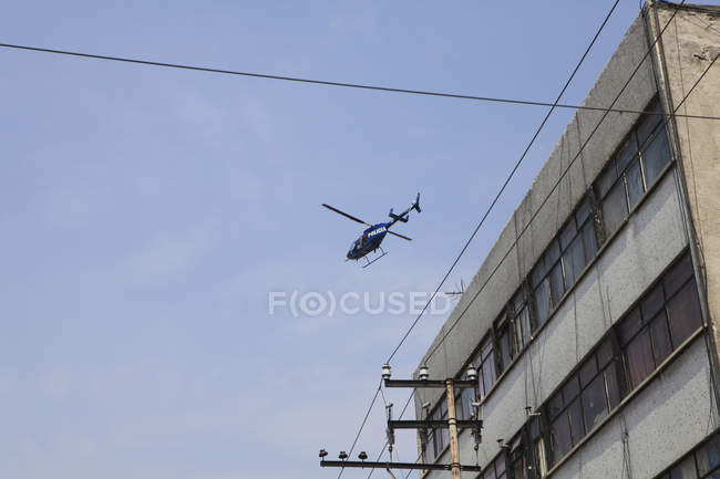 Low angle view of helicopter flying over building — Stock Photo