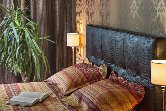 Book and pillows on cozy bed — Stock Photo
