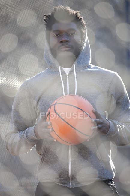 Young man holding basketball and standing on basketball court — Stock Photo
