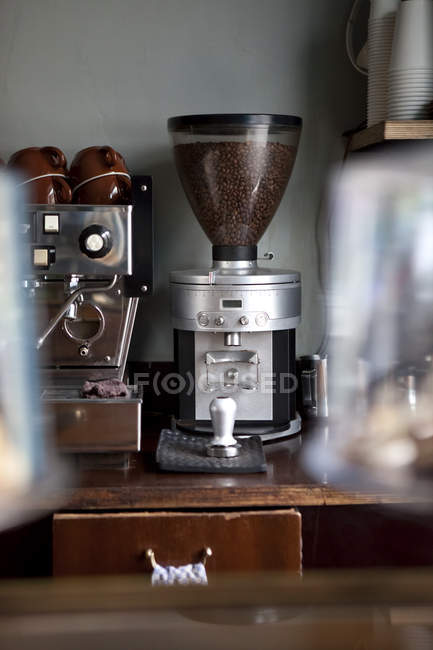Coffee bean grinder next to an espresso maker in coffee shop — Stock Photo