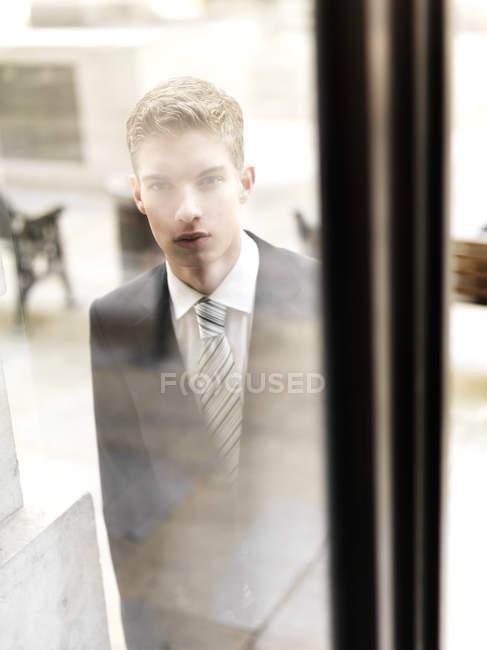 Молодой бизнесмен, прибывающий в здание, которого видят через окно — стоковое фото