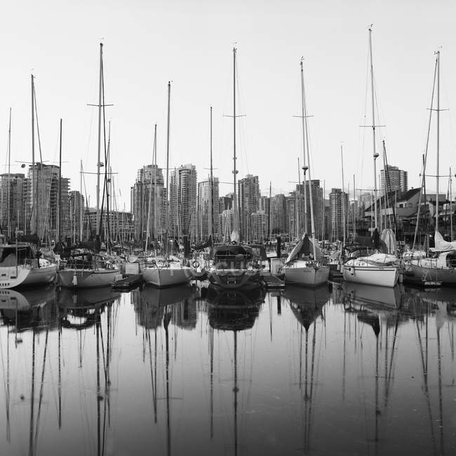 Skyscrapers and boats reflecting in water of marina — Stock Photo