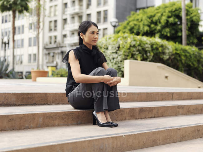 Contemplative businesswoman sitting on outdoor steps of office complex — Stock Photo