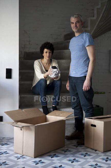 Retrato de embalaje de pareja mixta edad mover cajas de escalera en casa - foto de stock