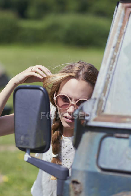 Junge Frau macht Haare, während sie in den LKW-Seitenspiegel schaut — Stockfoto