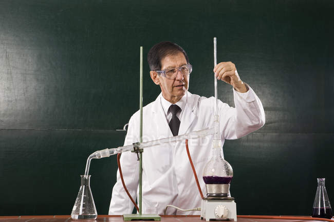 A chemistry teacher conducting an experiment in a classroom — Stock Photo