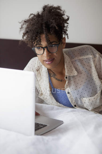 Woman using laptop on bed at home — Stock Photo