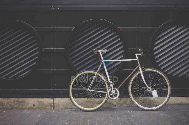 Vélo garé sur le trottoir à côté de la façade avec trous d'aération — Photo de stock