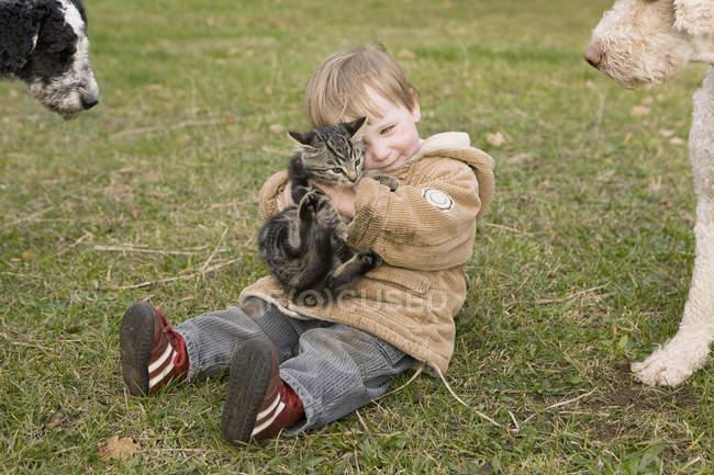 Bebé jugando con el gato mientras está sentado en la hierba - foto de stock