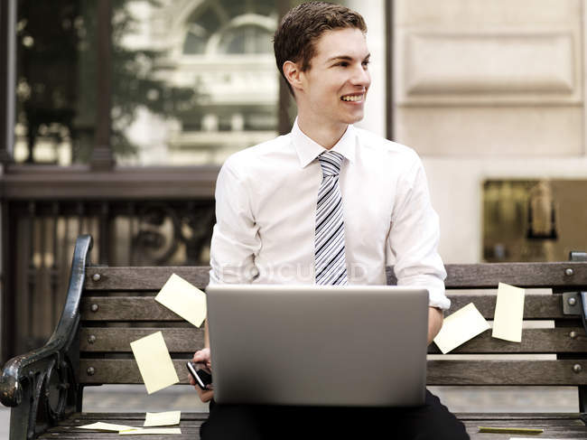 Smiling businessman holding smart phone while using a laptop sitting on bench with sticky notes — Stock Photo