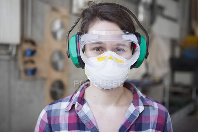 Portrait de menuisière en lunettes de protection et masque à l'atelier — Photo de stock