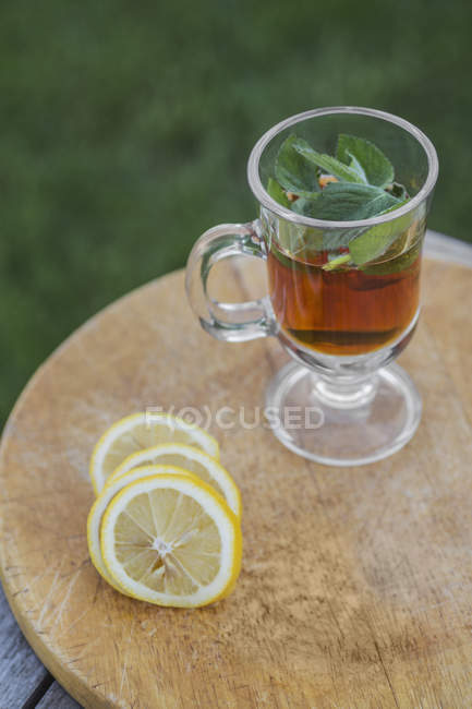 Iced tea with mint leaves anflime slices on outdoor table — Stock Photo
