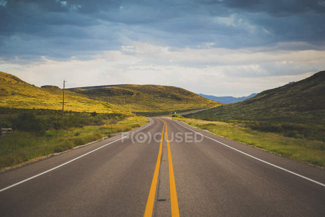 Road leading towards green mountains against cloudy sky — Stock Photo