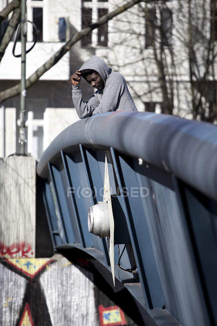 Nachdenklicher junger Mann steht auf Brücke und blickt nach unten — Stockfoto