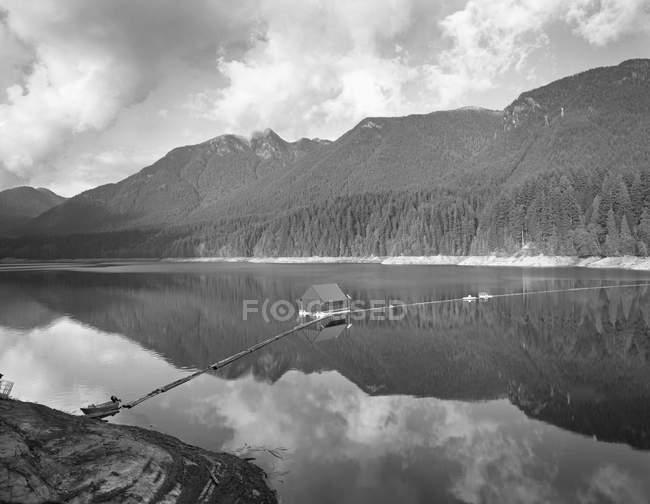 Живописный вид на озеро Капилано с сельским паромом и горным хребтом на заднем плане — стоковое фото