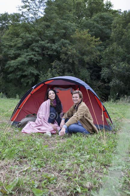 Souriante jeune couple assis près de la tente dôme dans la nature — Photo de stock