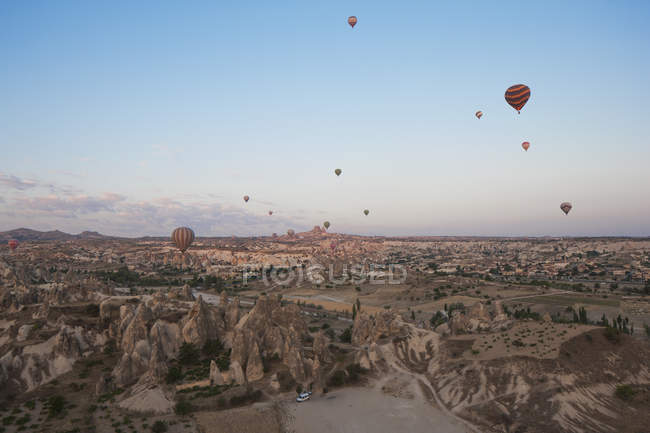 Hot air balloons flying in clear blue sky over rock formations landscape — Stock Photo