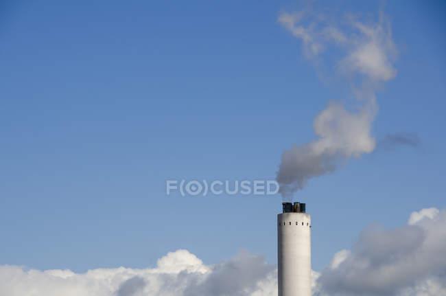 Дым, исходящий из дымохода промышленного здания на фоне голубого неба — стоковое фото