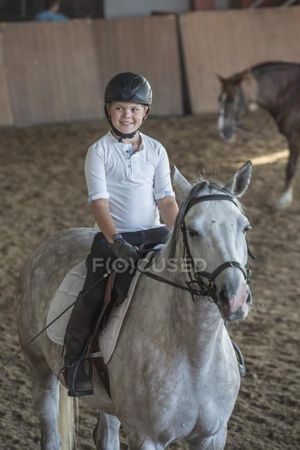 Menino equitação cavalo no treinamento estável — Fotografia de Stock