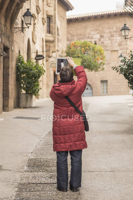 Rear view of woman photographing buildings with digital tablet — Stock Photo