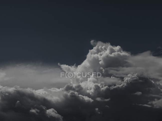 Colpo panoramico di cloudscape contro il cielo scuro — Foto stock