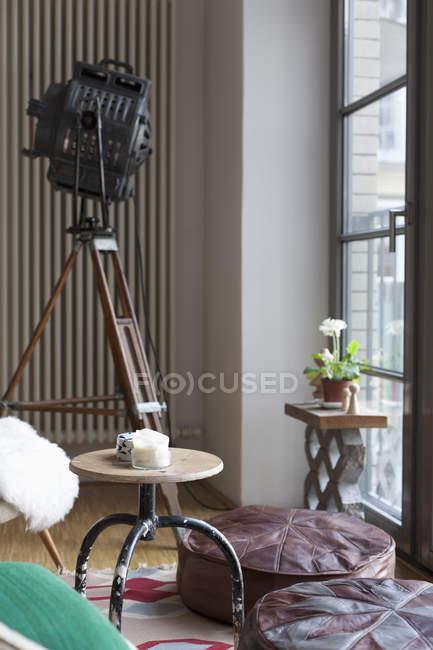 Spotlight on tripod placed at luxury interior beside window — Stock Photo