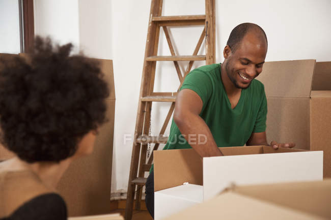 Couple packing moving boxes in apartment — Stock Photo