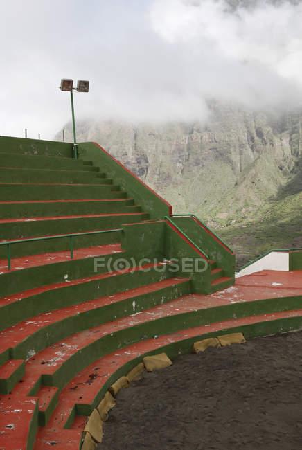 Ve a asientos vacíos en el campo de deportes en zona de montaña - foto de stock