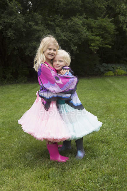 Portrait of happy girl hugging sister while standing in backyard — Stock Photo
