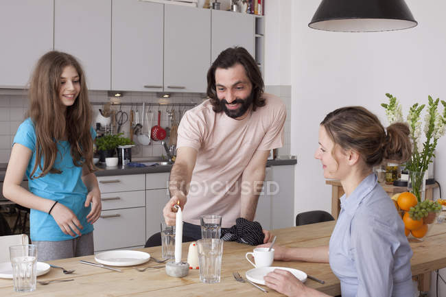 Smiling family arranging dinner table in kitchen — Stock Photo