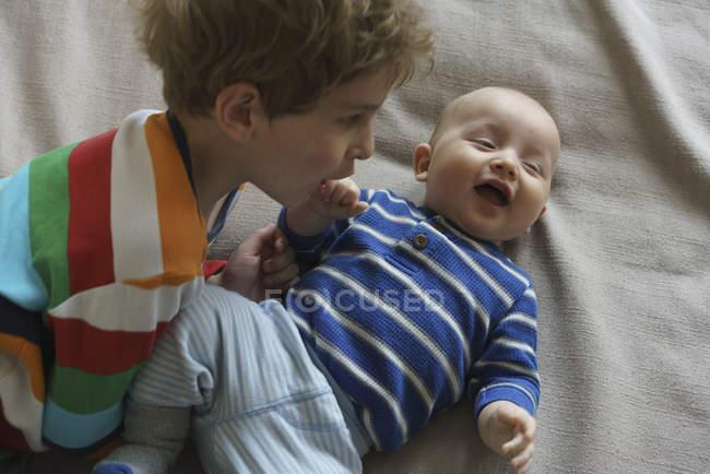Vista di alto angolo del ragazzo che gioca con il bambino sul letto a casa — Foto stock